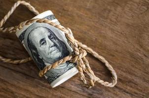 notas de cem dólares enroladas com corda foto