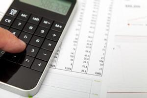 calculadora preta com figuras financeiras foto
