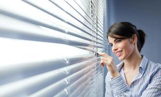 mulher atraente espreitar através das cortinas foto
