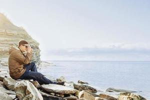 homem viajante tirando fotos na costa