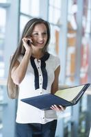 empresária no celular, segurando a pasta e sorrindo foto