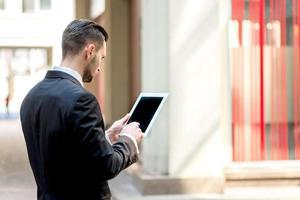 empresário trabalhando sobre o tablet. jovem com roupa formal foto