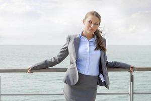 retrato de empresária confiante, apoiando-se nos trilhos do terraço foto