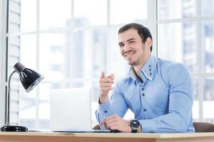 você está certo. empresário sorridente, trabalhando no seu laptop e poin foto
