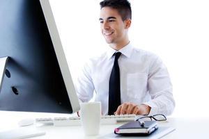 homem de negócios jovem feliz trabalhar no escritório moderno no computador foto