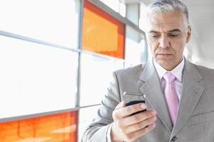 empresário envelhecido médio usando telefone inteligente na estação de trem foto