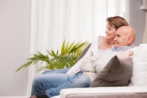 casal maduro assistindo tv no sofá foto