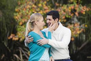 casal feliz abraçando no jardim foto