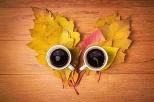 xícaras de café nas folhas de outono foto