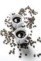 grãos de café em torno de dois expressos foto