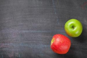 maçãs verdes e vermelhas no fundo do quadro-negro ou lousa foto