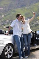 casal ao lado de carro estacionado na estrada, mulher tendo auto-retrato foto