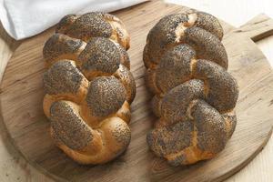 pão chalá fresco inteiro com sementes de papoila foto