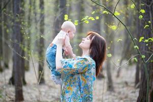 jovem mãe com seu filho em uma floresta de primavera foto