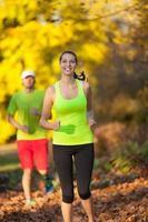 jovem casal correndo na temporada de outono foto