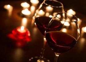 dois copos de vinho à luz de velas foto