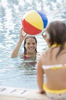mãe e criança brincando com bola de praia na piscina foto