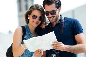 casal jovem turista na cidade segurando um mapa. foto