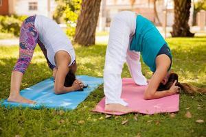 pose de ioga descendente em um parque foto