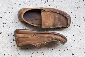 sapatos de couro velho no chão de tijoleira foto