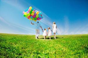 família feliz segurando balões coloridos. mãe, ded e dois daughte foto