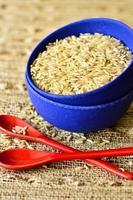 tigela de arroz seco e duas colheres foto