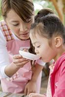mãe tendo criança sabor prato