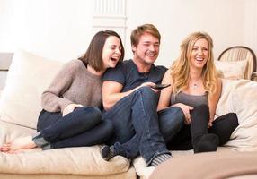 três adolescentes desfrutam de um programa de televisão engraçado foto