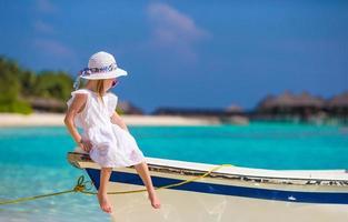 menina adorável barco durante as férias de verão foto