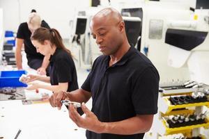 trabalhadores na fábrica de engenharia, verificando a qualidade dos componentes