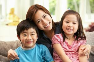 mãe chinesa e filhos sentados juntos no sofá em casa