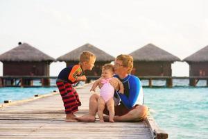 pai com filhos de férias tropicais