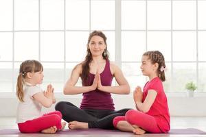 jovem mãe e filhas fazendo exercícios de ioga