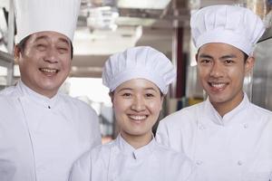 três chefs em uma cozinha industrial foto