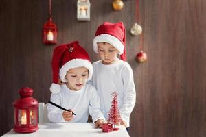 dois meninos adoráveis, escrevendo a carta para o Papai Noel foto