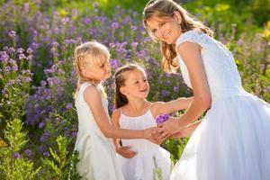 linda noiva e floristas em campo de flores roxas foto