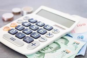 calculadora com dinheiro em fundo cinza foto