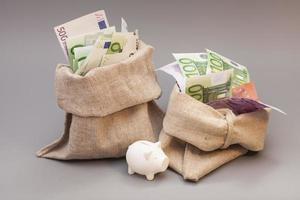 saco de dois dinheiro com euro e cofrinho foto