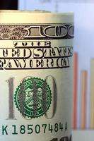 gráfico de vendas e moeda dos EUA notas de cem dólares foto