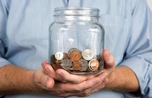 segurando um pote de dinheiro moedas foto