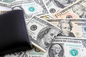 carteira de couro preto com dinheiro dólares foto