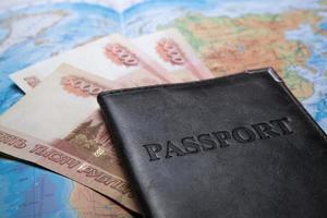 passaporte na bolsa em um mapa com notas de banco foto