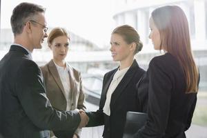 empresários confiantes, apertando as mãos no local de trabalho foto