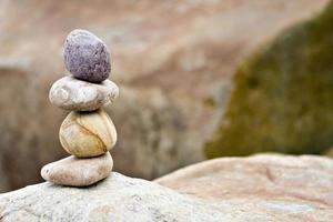 equilibrando pedras em uma pedra grande foto
