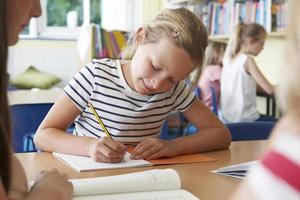 aluno da escola primária, trabalhando na mesa na sala de aula foto