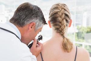 médico examinando uma mancha em seu paciente foto