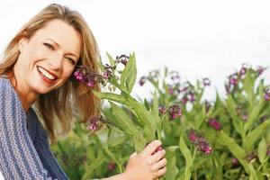 mulher ao lado de uma planta de consolda foto