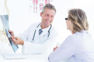 médico mostrando o raio x para seu paciente foto