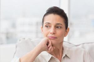mulher pensativa, sentada no sofá