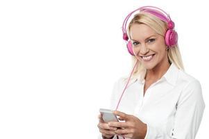 mulher sorridente, apreciando a música com seu telefone celular foto